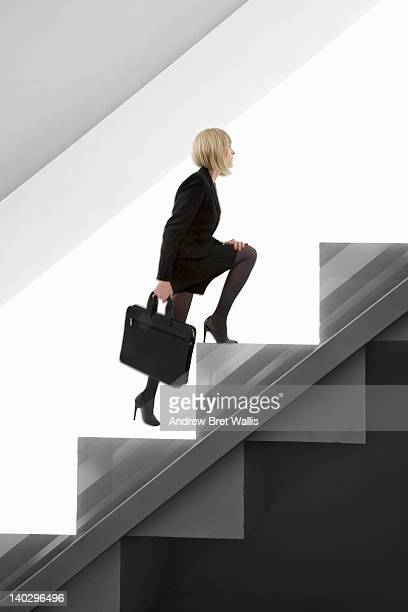 Little businesswoman climbs giant stairs