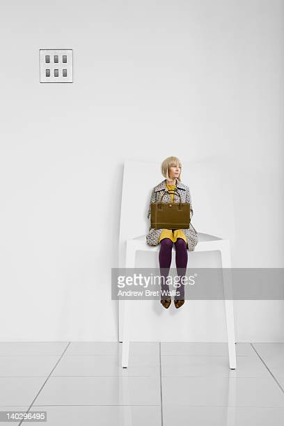 little businesswoman waits in a giant office chair - tamanho desproporcionado - fotografias e filmes do acervo