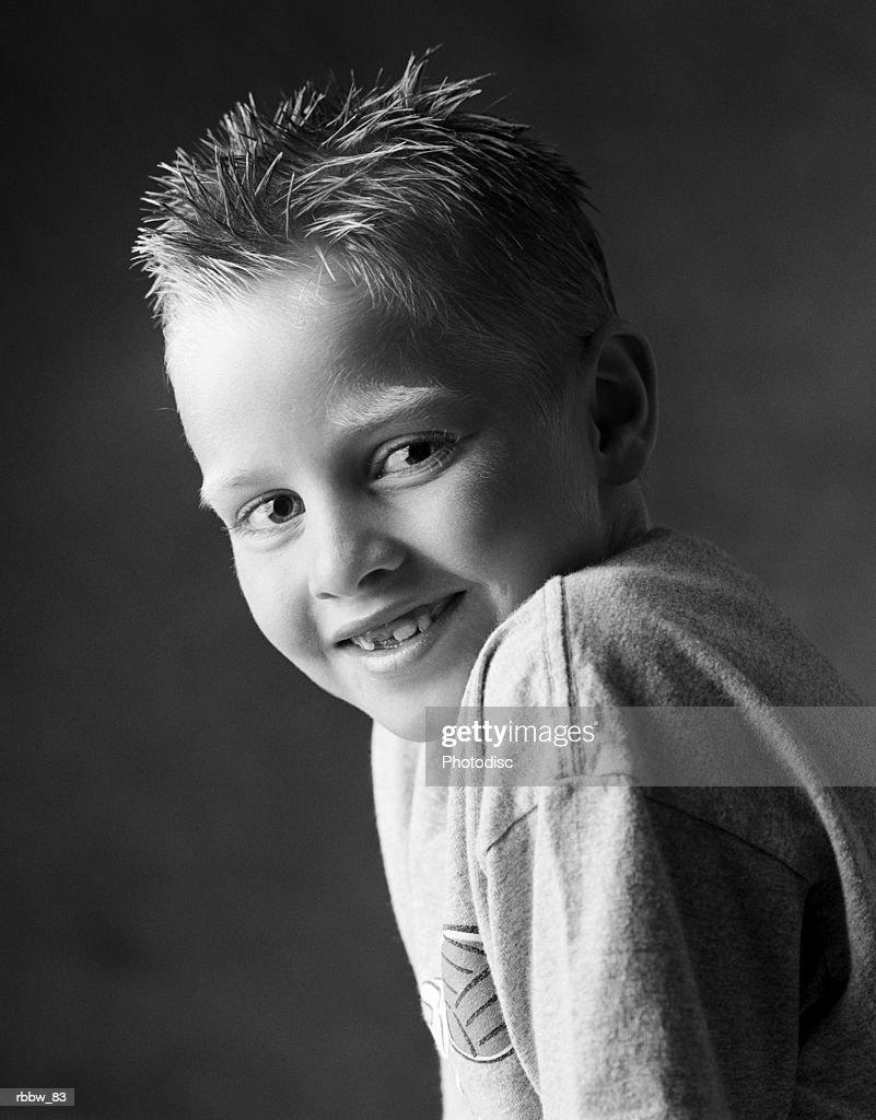 A little caucasian boy smiles over his shoulder : Stockfoto