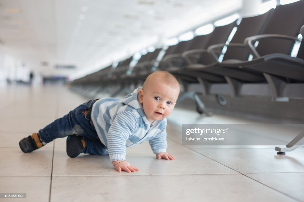 Little child, baby boy, playing at the airport, while waiting for his plane to departure : Stock Photo