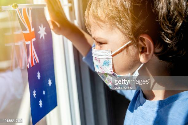 little child boy looking through a window using a surgical mask holding a an australian flag - coronavirus australia stock pictures, royalty-free photos & images