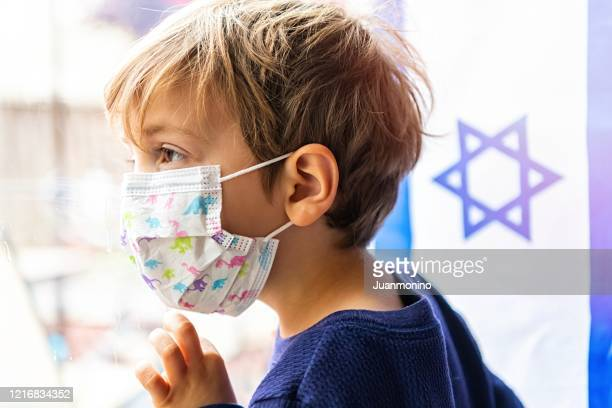 little child boy looking through a window using a surgical mask with an israeli flag in the background - israel stock pictures, royalty-free photos & images