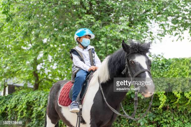 little child boy with protective face mask riding pony horse - jockey silks stock pictures, royalty-free photos & images