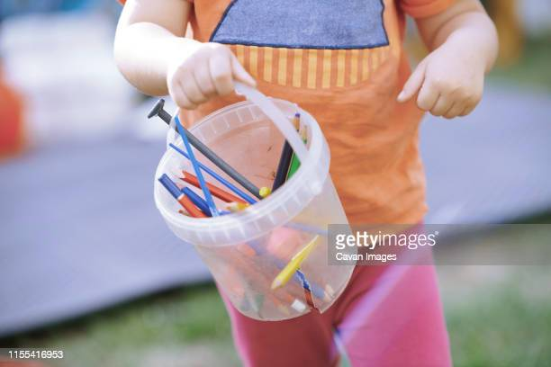 little child carrying the bucket with colored pencils - unrecognisable person stock pictures, royalty-free photos & images