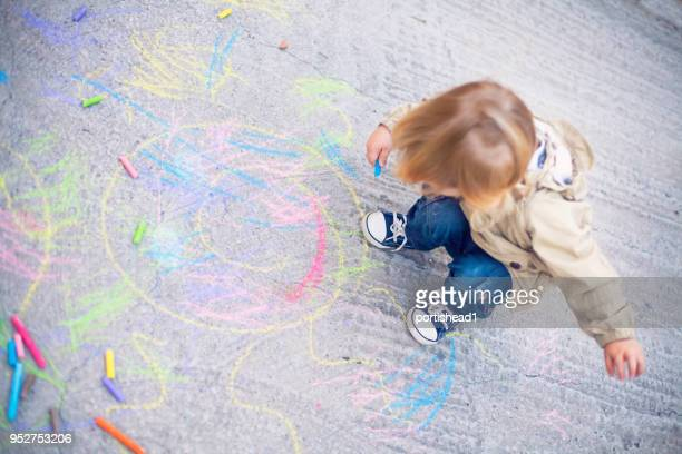little child drawing with sidewalk chalks - careless stock pictures, royalty-free photos & images
