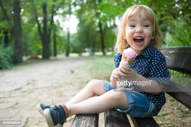 Little child eating ice cream in a park