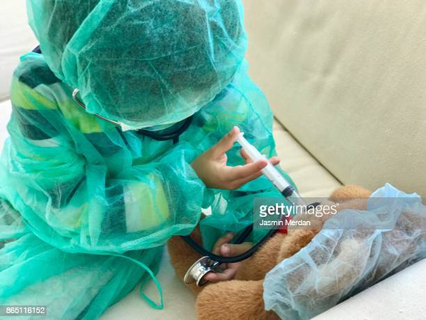 Little child giving injection to his Teddy bear