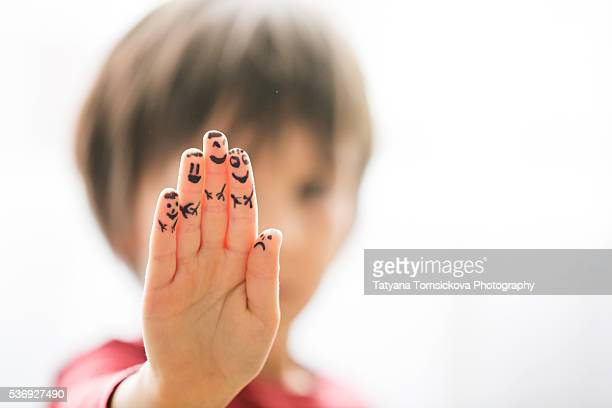 Little child hand, fingers painted with smiley faces, isolated on white background
