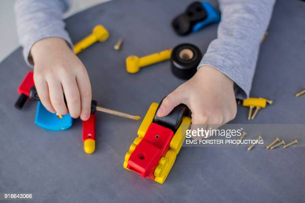 little child is playing and screwing with wooden toys