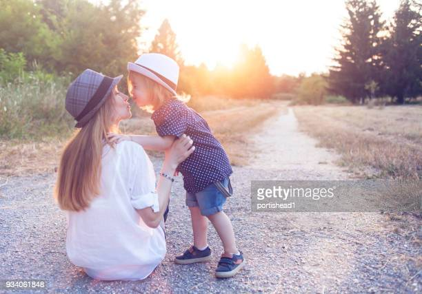 little child kissing his mother - hot mom stock photos and pictures