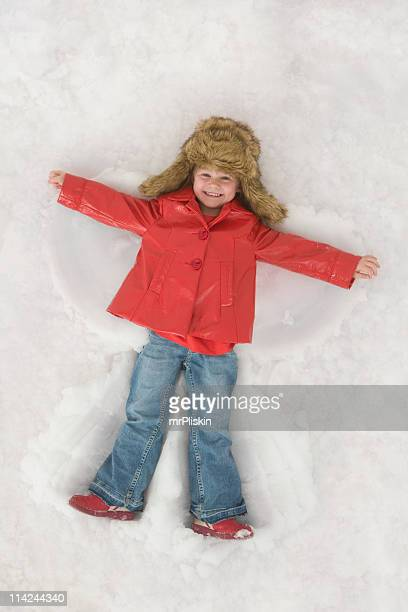 little child making a snow angel - snow angel stock photos and pictures