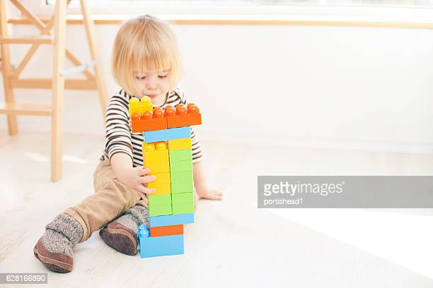 Little child playing with colorful plastic blocks