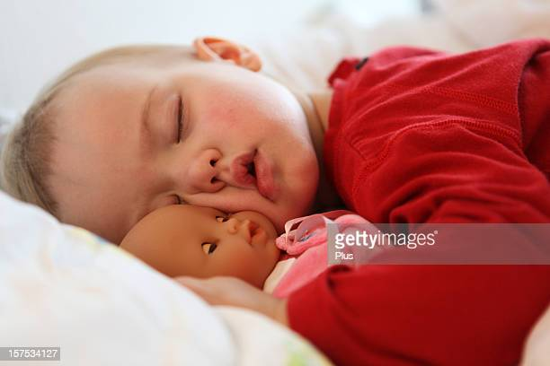 Little child sleeping with doll
