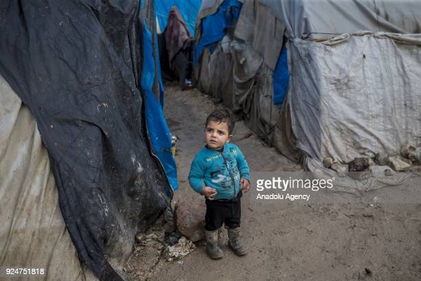 A little child stands on a muddy surface on a winter day at Babussalam refugee camp in Azez Syria on February 26 2018