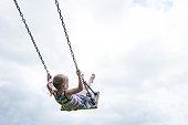 Little child swinging on a wooden swing