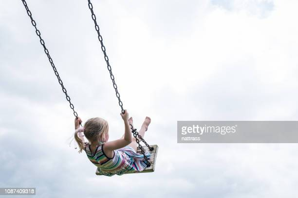 little child swinging on a wooden swing - swinging stock pictures, royalty-free photos & images