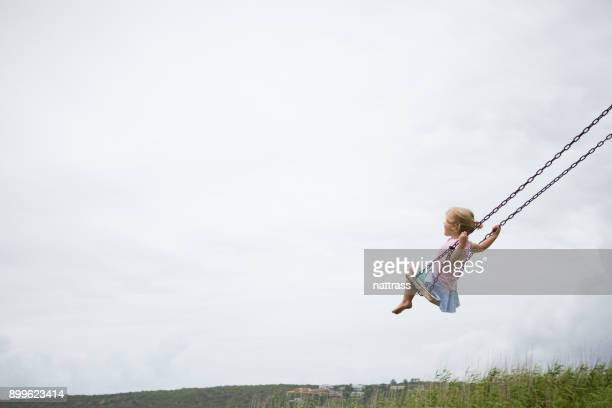little child swinging on a wooden swing - copy space stock pictures, royalty-free photos & images