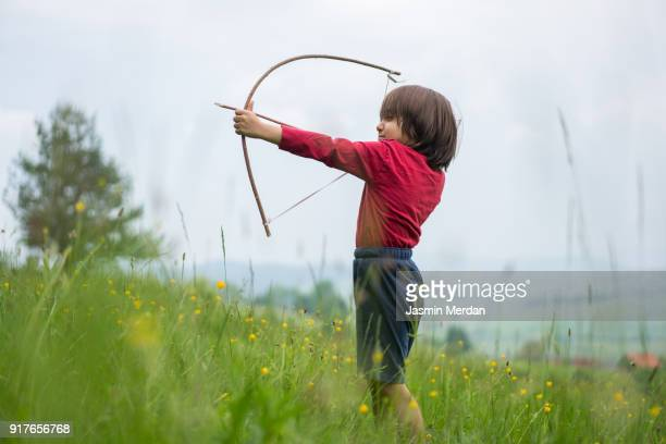 Little child with bow and arrow in field