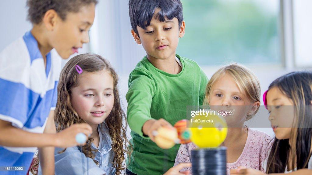 Little Children Exploring a Model Solar System : Stock Photo