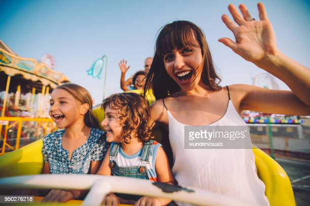 Little children having fun with mother on roller coaster ride