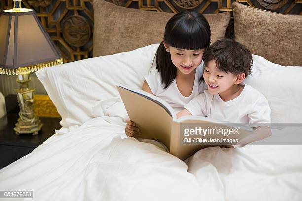 Little children reading a book in bedroom
