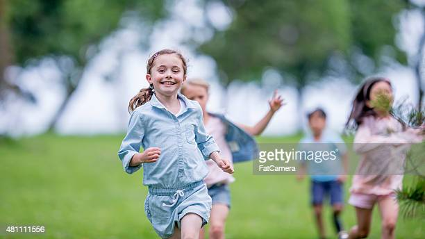 little children running outdoors - kids playing tag stock photos and pictures