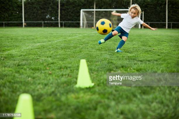 little children shoots a perfect soccer volley. - shooting at goal stock pictures, royalty-free photos & images
