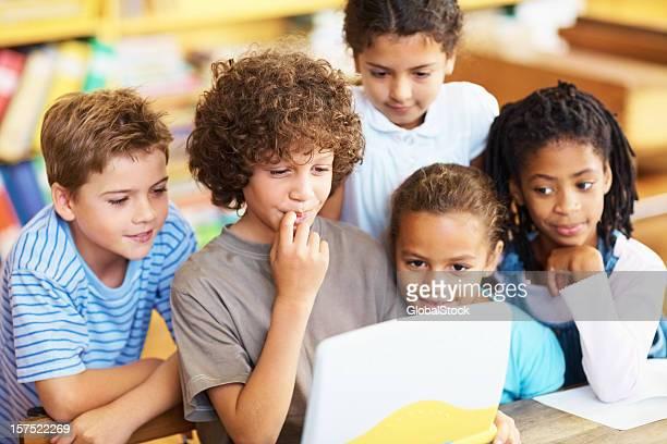 Little children using a laptop at school