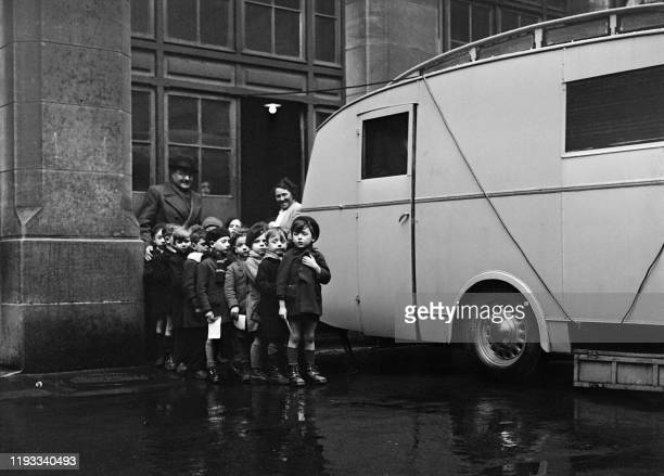 Little children wait before having an xray radiography of the lungs during a tuberculosis screening operation in schools in January 1946 in Paris