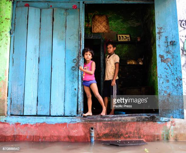 Little children wait eagerly for the water to reside around their house so that they can go about their afternnon playtime Monsoon season in kolkata...