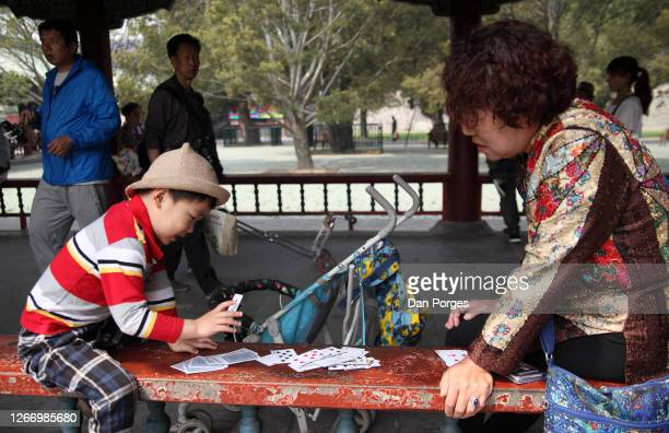 A little Chinese boy 34 years old and his grandmother play cards for fun in the Temple of Heaven compund the boy's stroller stands next to them...