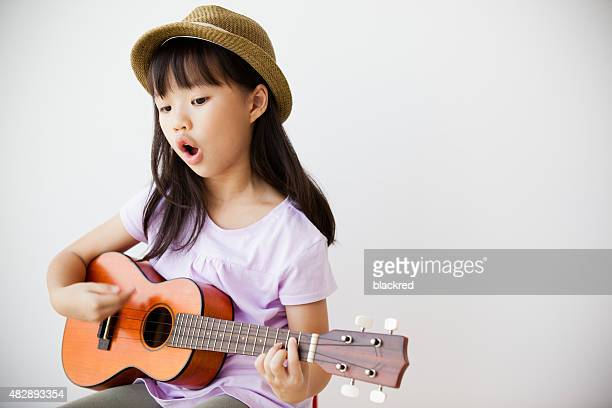 little chinese girl singing and playing ukulele - chinese music stock pictures, royalty-free photos & images