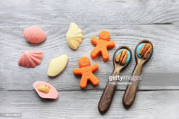 little chocolate figures. spoons, little men, shells on wooden background. sweet art and food. - nuts models stock pictures, royalty-free photos & images