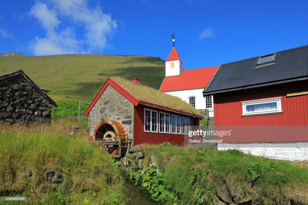 A little church behind a watermill with grassy roof in a small village : Stock-Foto