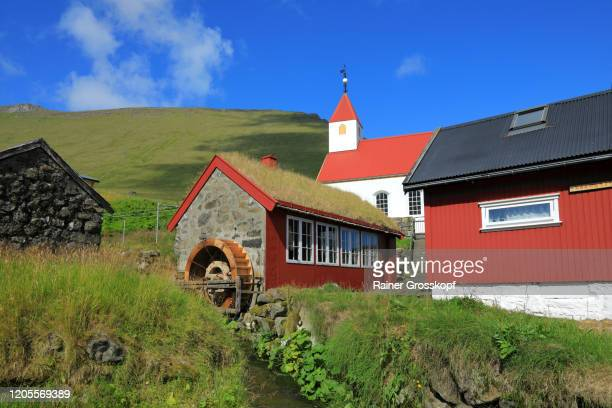 a little church behind a watermill with grassy roof in a small village - rainer grosskopf stock pictures, royalty-free photos & images