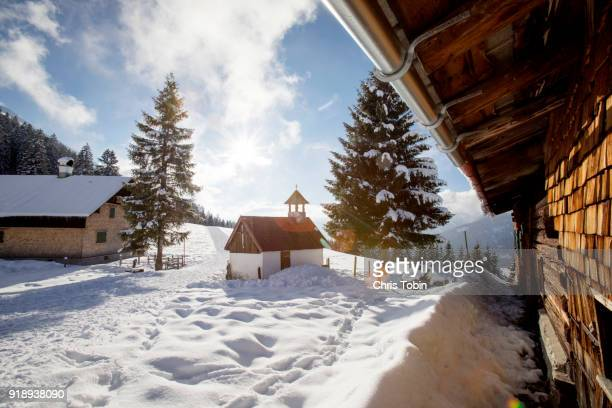 little church in the snowy mountains near a farm - oberstdorf stock pictures, royalty-free photos & images