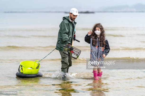 Little Claudia Basallo niece of shellfisherman Adrián González holds a clam caught by her uncle on May 12 2020 in A Pobra do Caramiñal Spain The...