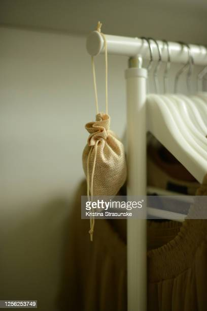 little cloth bag, filled with dried rose petals, hanging on a clothing rack by clothes - kristina rose fotografías e imágenes de stock