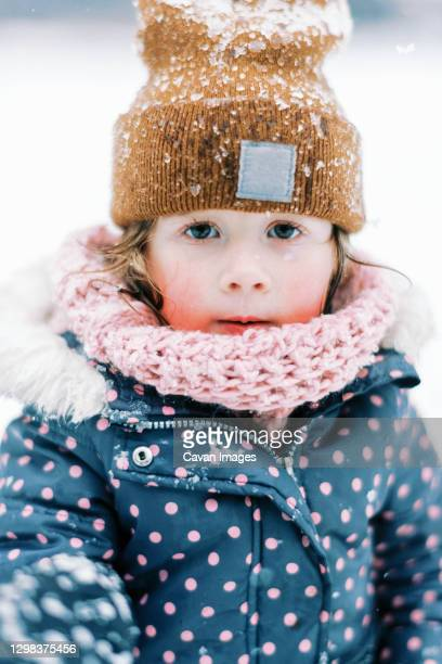 little cold toddler girl freezing outside with snow on hat and face - damp lips stock pictures, royalty-free photos & images