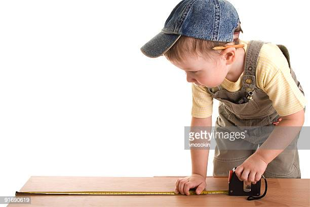 Little construction child with tape-measure