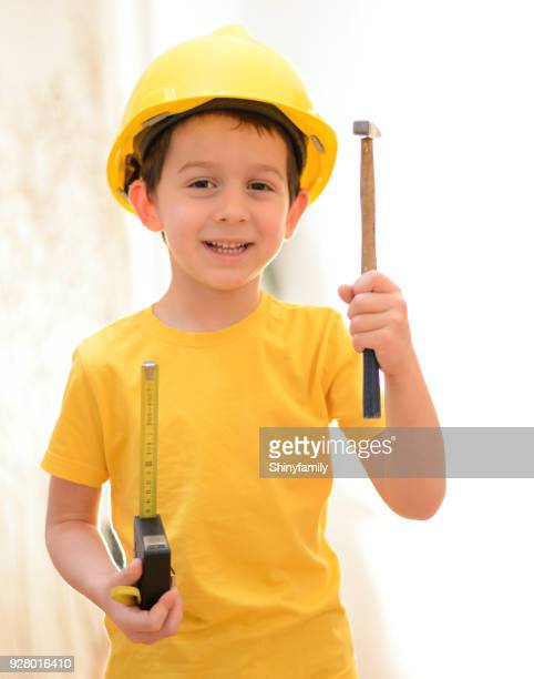 Kleine bouwvakker met handgereedschap en hard hat
