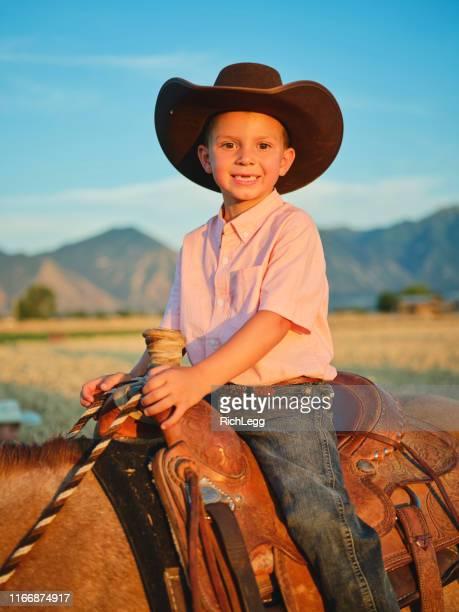liten cowboy rida sin ponny häst - pony play bildbanksfoton och bilder
