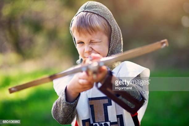 Little crossbowman aiming at the camera
