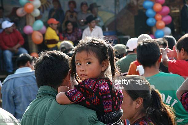 little curious mayan girl with her parents in chichicastenango, guatemala - guatemala stock pictures, royalty-free photos & images
