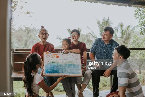 little cute art product of granddaughter shows to family-stock photo - painting art product stock pictures, royalty-free photos & images