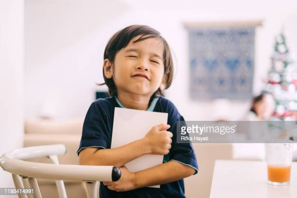 little cute asian boy hugging a book - one boy only stock pictures, royalty-free photos & images