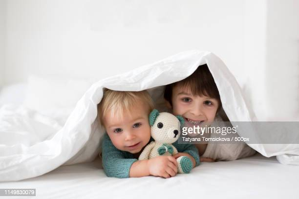 little cute baby boy and his older brother, children in knitted - oreiller geant photos et images de collection