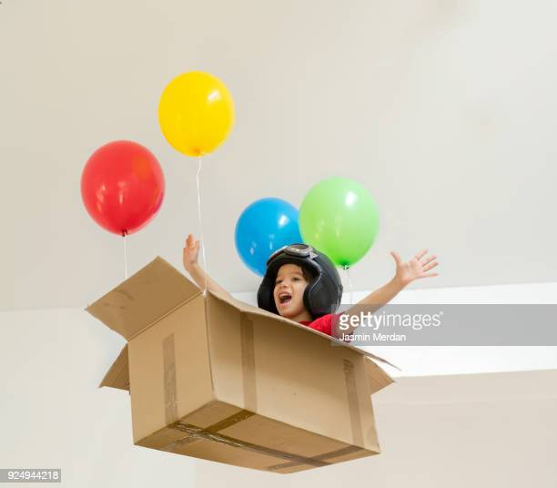 Little cute boy flying in box with balloons