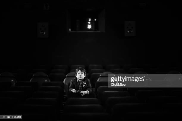 little cute boy on the cinema in the dark - click&boo fotografías e imágenes de stock