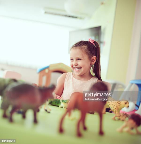 little cute female girl playing and learning the animals in classroom - toy animal stock photos and pictures